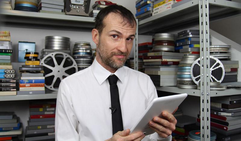 Daniele Carrer con un tablet di fronte alla sua collezione di film trasferiti da super 8 a digitale