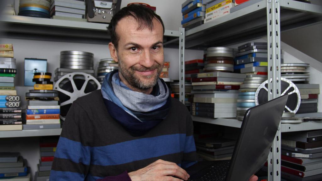 Daniele Carrer di fronte alla sua collezione di film 8 mm amatoriali
